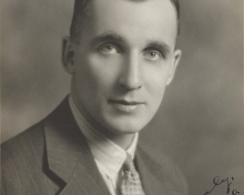 An old photograph of a young Dr. Harry Botterell in suit and tie shot from the chest up.