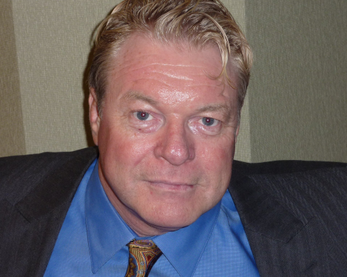 head and shoulders shot of Dave in suit jacket, blue shirt and tie