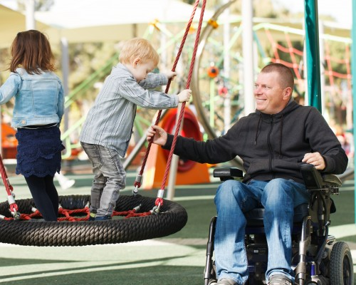 Dad using wheelchair playing with two young children on a swing