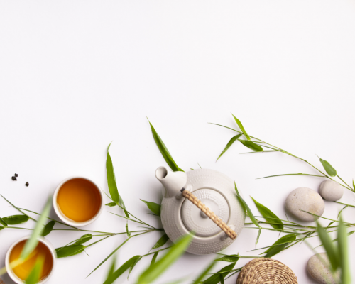 Loose leaf tea, lemon grass and a tea pot with a white background