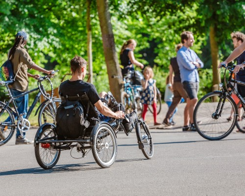 a group of bikers including a person with a hand cycle