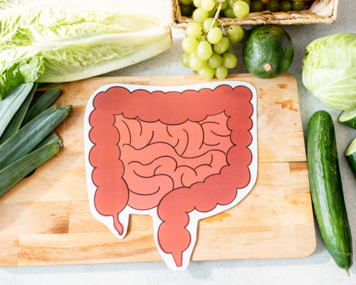 paper cut out of a bowel on a cutting board with fruit and vegetables around it
