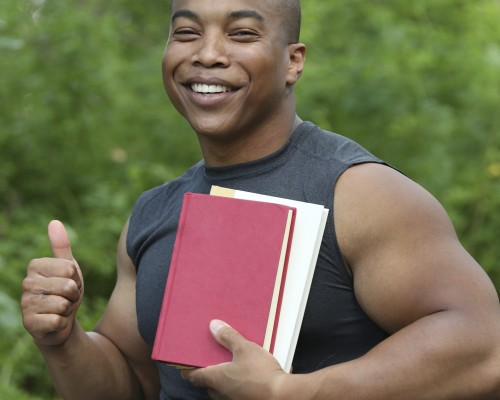 a smiling muscular student sitting in his wheelchair hold books in one hand and thumb up with the other