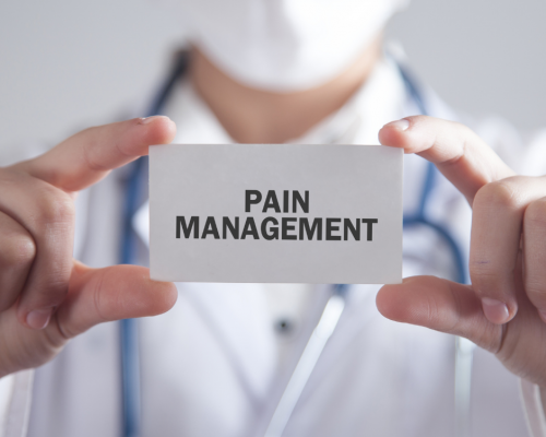 doctor holding up card that says 'pain management'