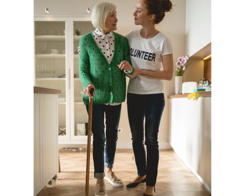 Woman helping a woman with a cane walk across a room at home