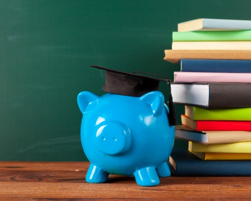 piggy bank with scholar cap and stack of books beside