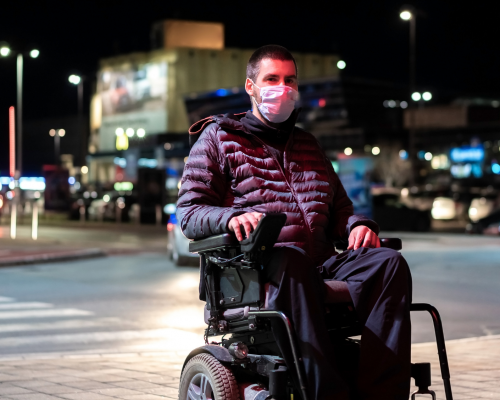 Man using power chair on the street wearing a mask
