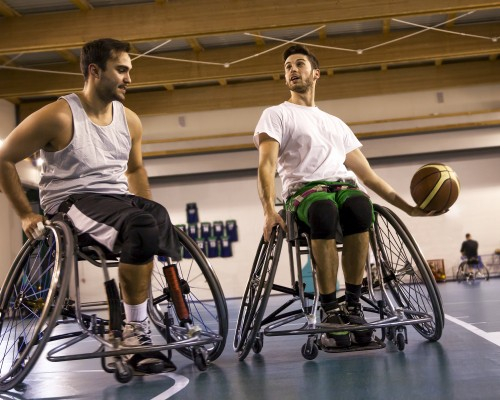 Two guys in sport wheelchairs playing basketball