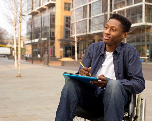 student sits in his wheelchair on university campus holding books