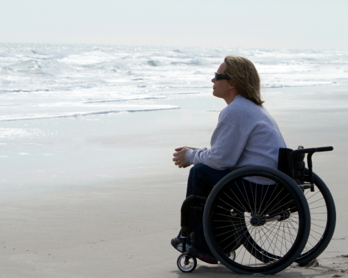 Woman using wheelchair on the beach