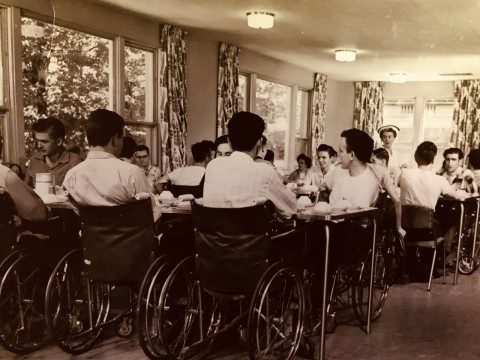 Many men sitting at tables in Lyndhurst Lodge ready for a meal.