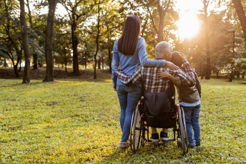 a mom, dad with a spinal cord injury and child