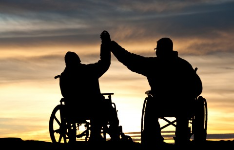 Two guys with spinal cord injuries giving each other a 'high five'