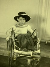 8 year old Edmond Derion sitting in his wheelchair sporting a black cowboy hat