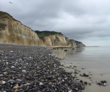 The Dieppe beach with cliffs in the background and a pebbled beach
