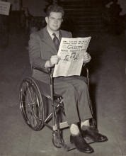 Donald Curren sits in his wheelchair reading a newspaper.