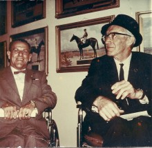 Jimmy Darou and John Counsell together sitting in their wheelchairs with race horse paintings and photos behind them.